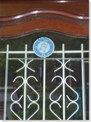 Frans Bauer style getraliede voordeur, met daarboven het bordje dat aangeeft dat wij hier met een erkend postzegelhandelaar te maken hebben